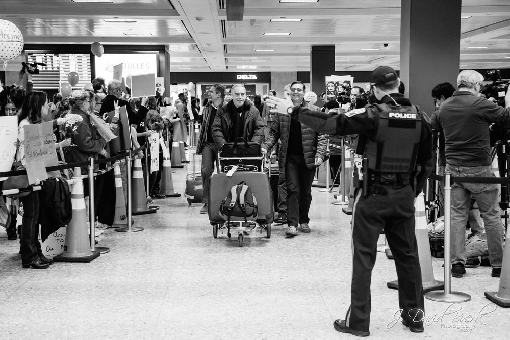 A Metropolitan Washington Airports Authority police officer directs passengers' traffic as they exit the International Arrivals Building after clearing customs.  Protestors fill both sides of the exit pathway which is normally surrounded with people awaiting the arrival of their friends and family.