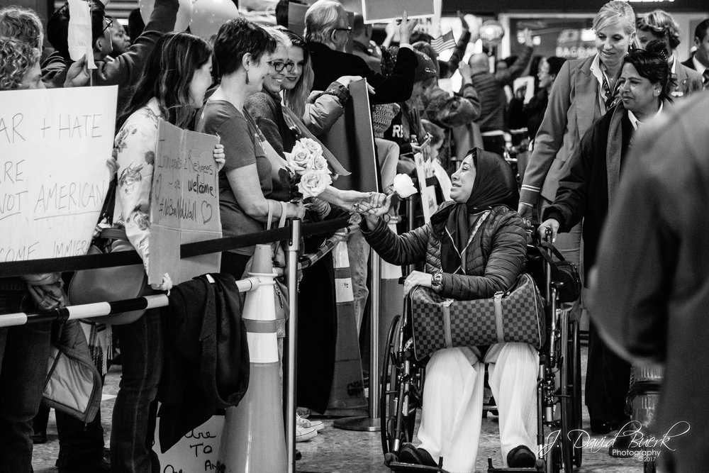 A protestor gives a white rose to an arriving international passenger.  White roses are traditionally known to represent purity, innocence, sympathy, and spirituality.