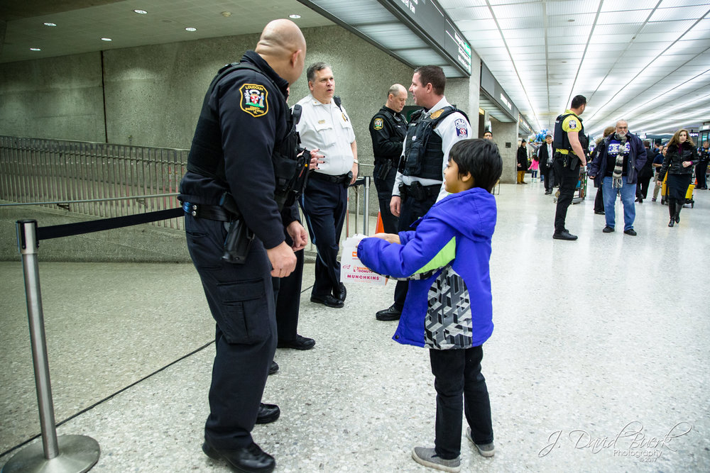 A young protestor offers Loudoun County and Metropolitan Washington Airports Authority police officers donuts and water and thanks them for keeping the demonstration safe.