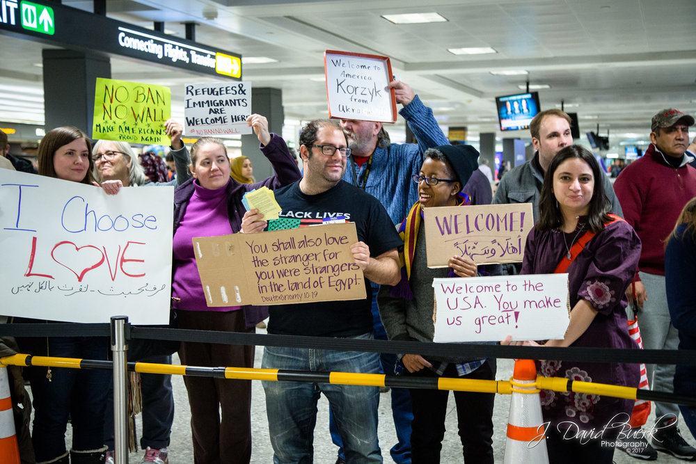 Protestors fill both sides of the International Arrivals Building exit pathway which is normally surrounded with people awaiting the arrival of their friends and family.  Greetings and welcomes were given to each individual arriving passenger, with cheers each time the IAB doors opened.