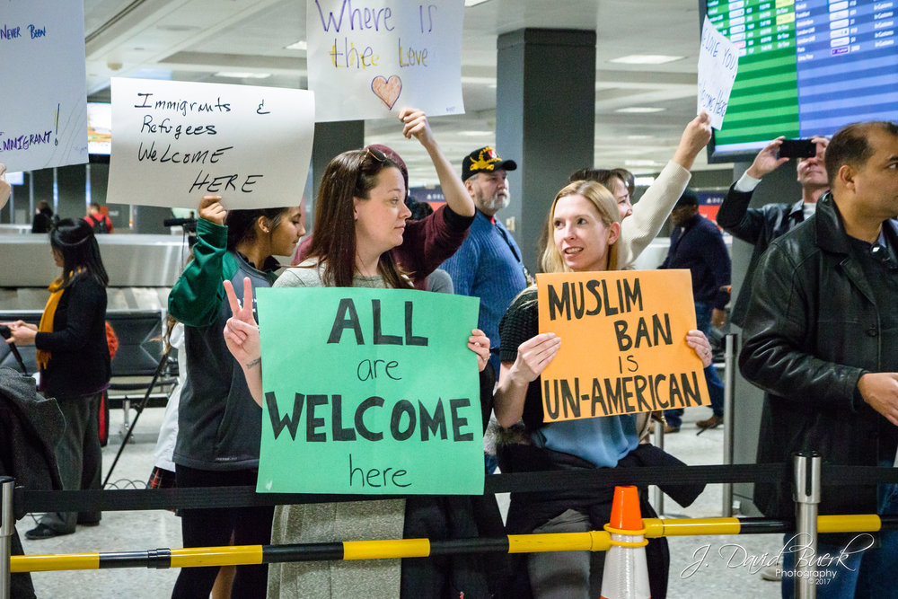 "A woman shows a peace sign while holding a sign; ""ALL are WELCOME here."""