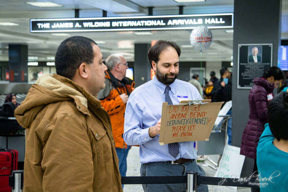 Volunteer lawyers and translators held signs to readily identify themselves to passengers and family who need legal counsel.