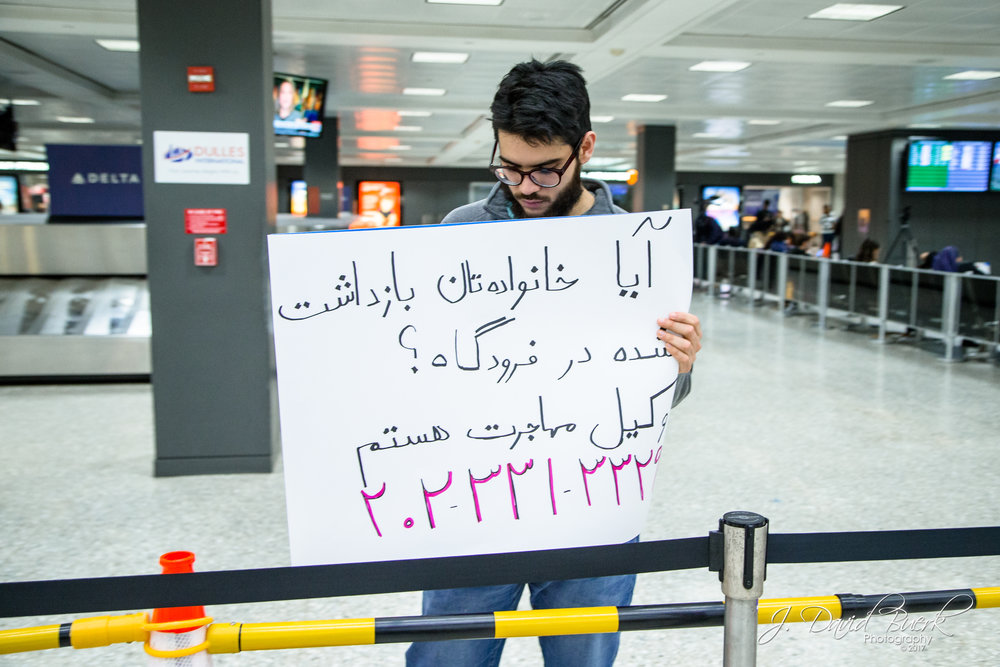 A man holds a sign in (language confirmation pending) outside the International Arrivals Building. (Translation pending.)