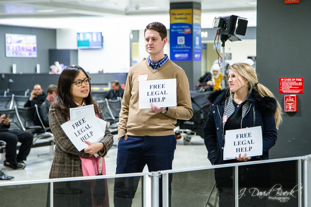 "Volunteer lawyers stand close to the International Arrival Building's exit with clearly legible signs reading, ""FREE LEGAL HELP.""  When news of the travel ban broke on Saturday, lawyers and translators converged upon airports to donate their time and efforts in investigating and protecting against civil liberty violations."