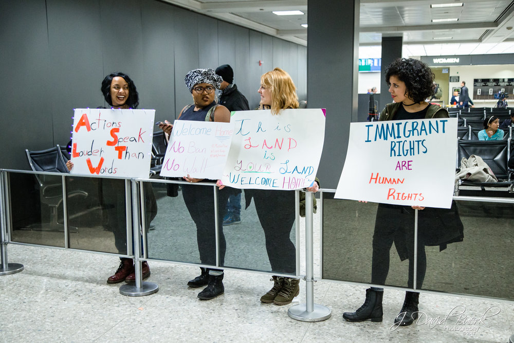 "Four women hold signs next to the International Arrival Building's exit; one woman's sign had flashing lights, reading, ""Actions Speak Louder Than Words."""