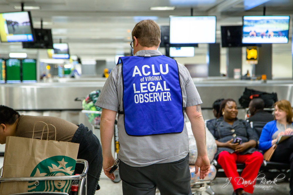 An American Civil Liberties Union legal observer in a blue high-visibility vest.  When news of the travel ban broke on Saturday, lawyers, translators, and legal observers converged upon airports to donate their time and efforts in investigating and protecting against civil liberty violations.  The ACLU was quick to file a lawsuit in opposition to the executive order, resulting in an emergency stay granted by Brooklyn Federal Judge Ann Donnelly late Saturday night, which allowed travelers caught in the ban's rapid rollout to be released from detention.