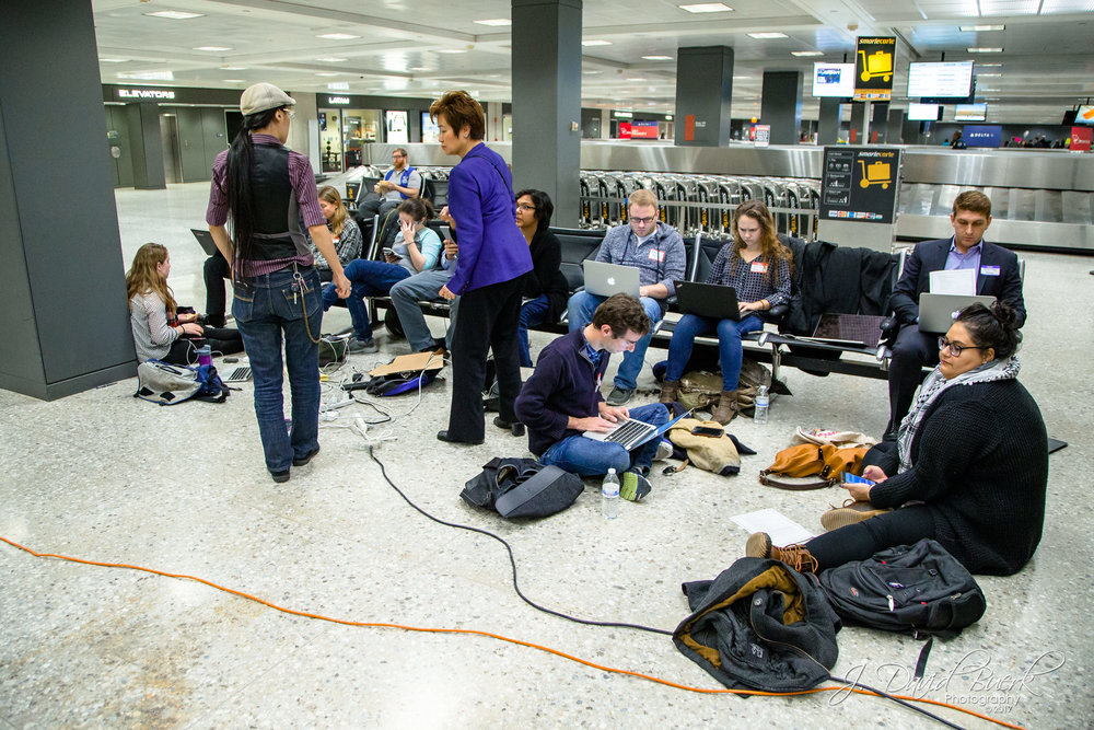 A group of volunteer lawyers working in the baggage claim area of Washington Dulles International Airport.  When news of the travel ban broke on Saturday, lawyers, translators, and legal observers converged upon airports to donate their time and efforts in investigating and protecting against civil liberty violations.