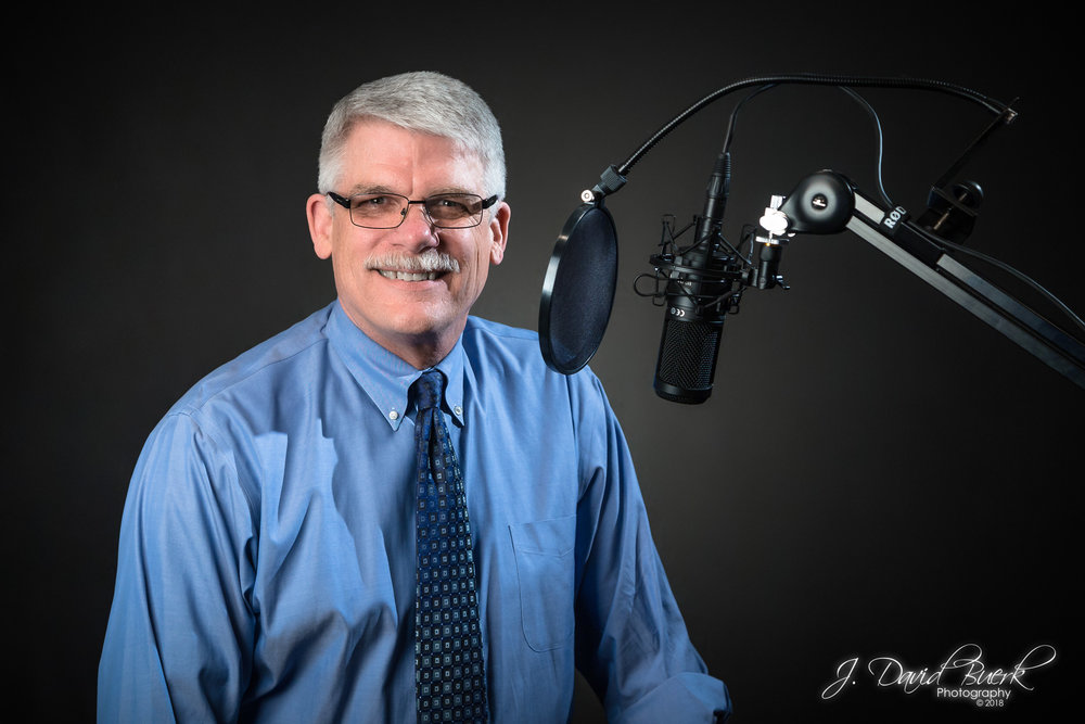 Portrait of Steve Mohyla CFP with podcasting microphone.