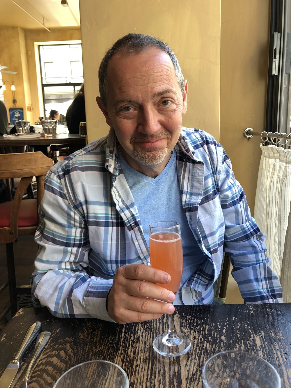 Bevan Dufty clutches a strawberry Bellini at Café de la Presse in Union Square at 4:24pm PST on April 21, 2018 while taking a break from shoe shopping with Partner Corey Lambert.