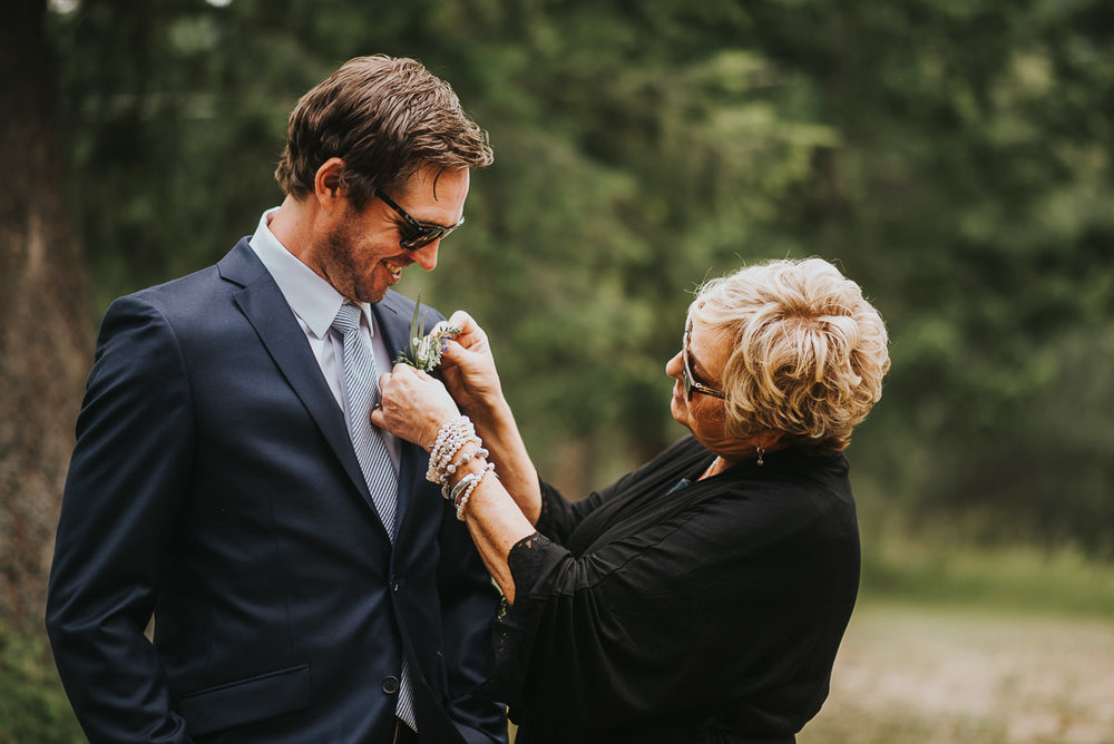 Alberta ranch wedding groom and mom putting on boutonniere
