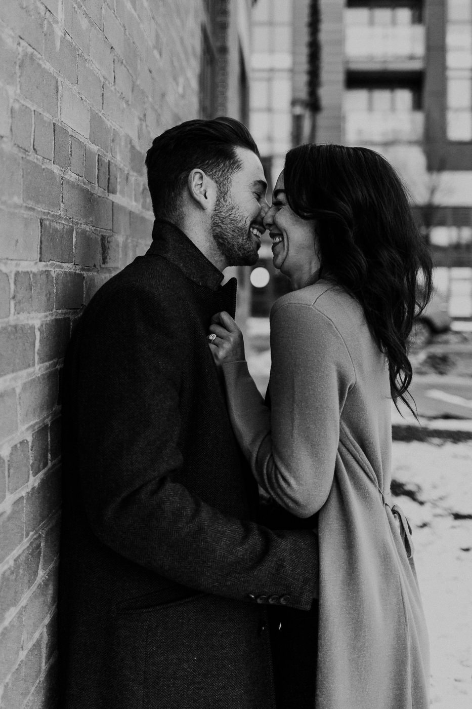 Black and white image of couple snuggling against a brick wall in downtown Calgary
