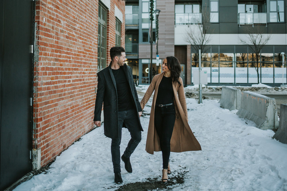 Couple walking together laughing at their downtown Calgary engagement session