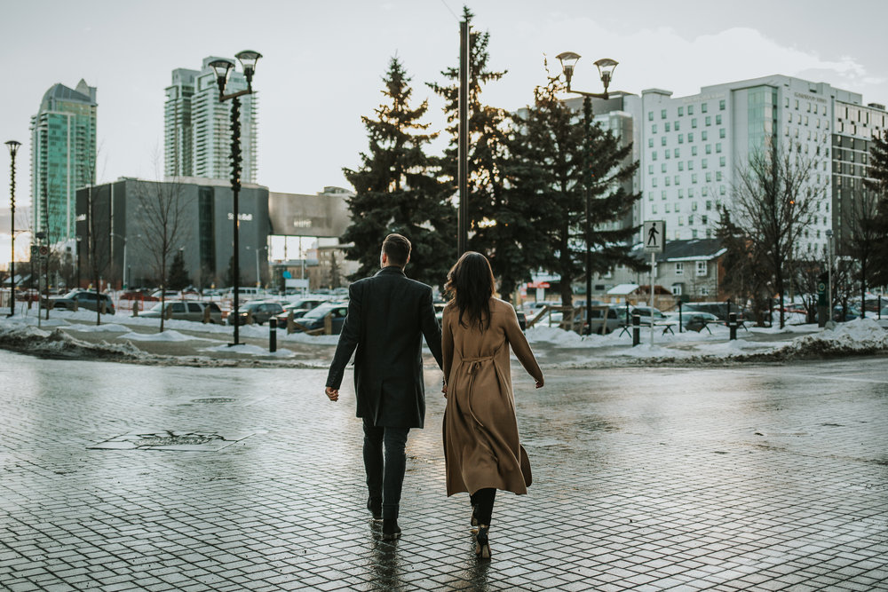 Cole walking across the street in downtown Calgary at their engagement session