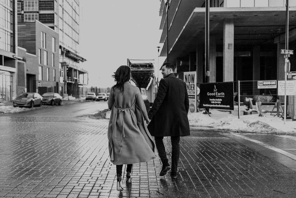 black and white photo of glamorous couple crossing the street ini a trench coat