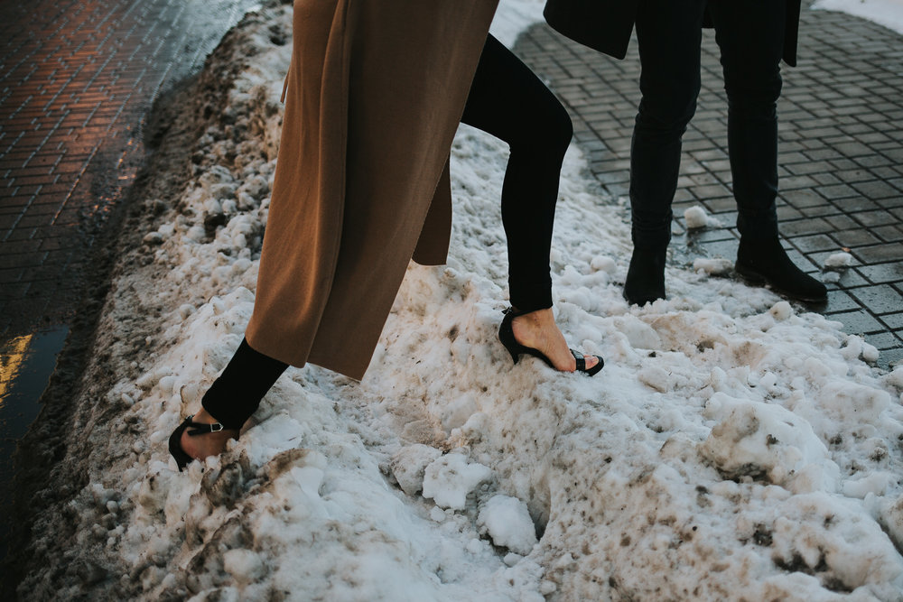 Girl walking through snowbank in high heels