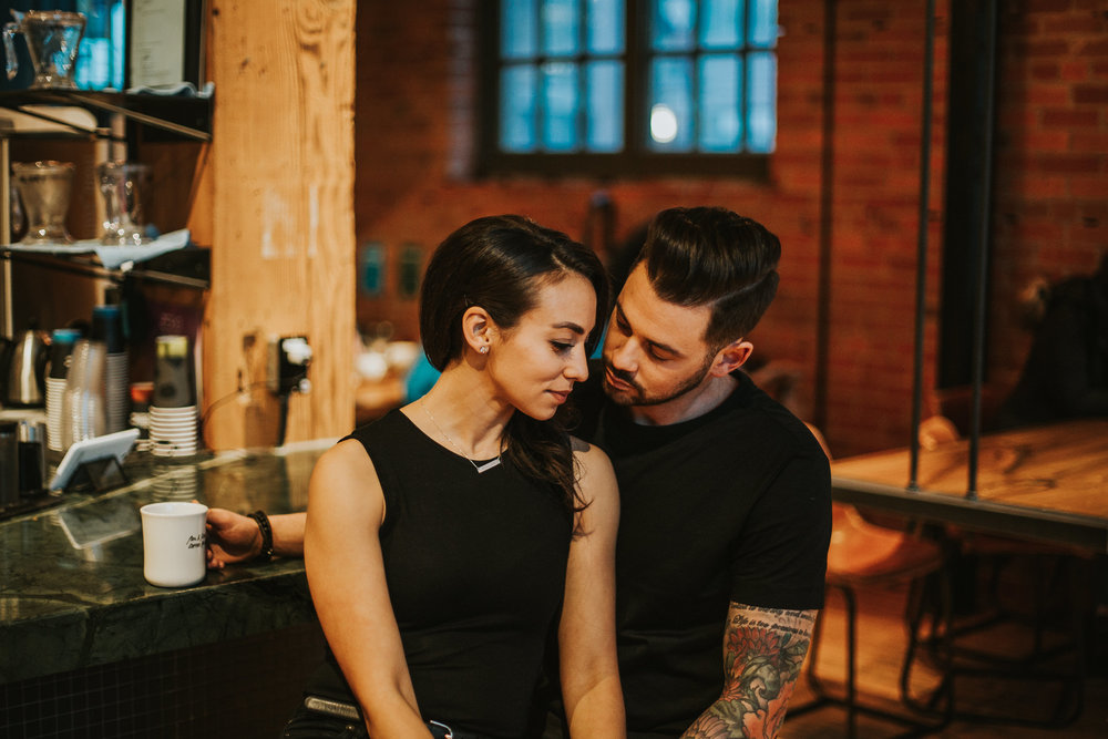 Couple enjoying coffee in brick walled coffee shop in Calgary