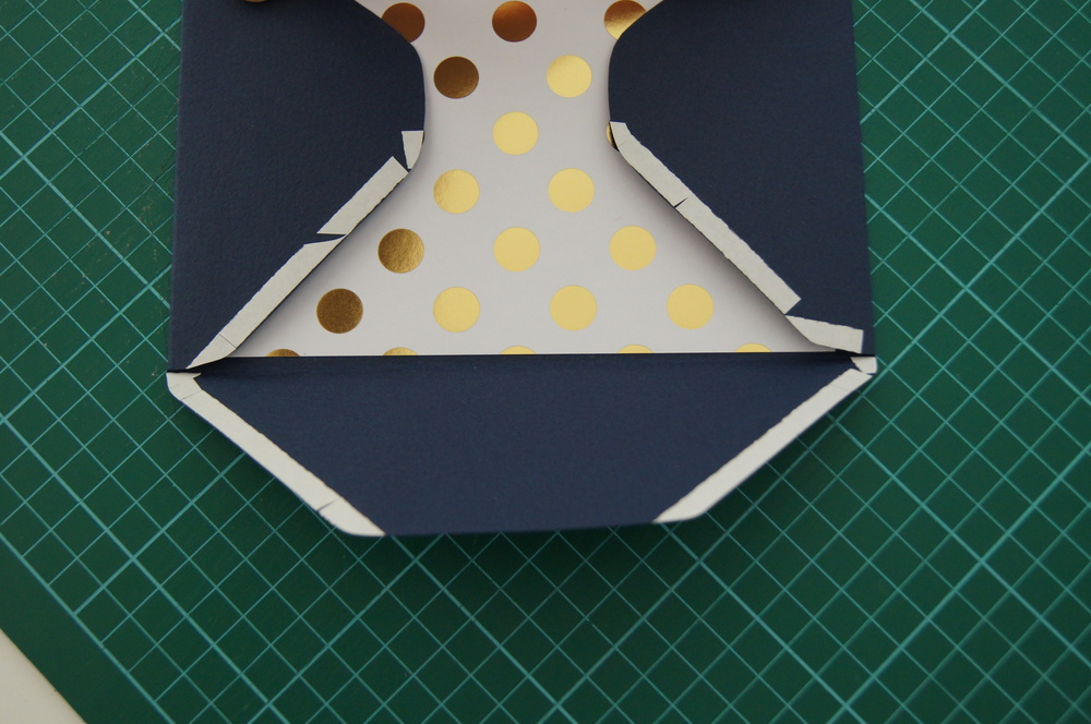 Be careful when placing your tape as you don't want the navy cardstock to stick to the gold and white polka dot cardstock, otherwise you won't be able to insert your invitations. Once again leave the protectant layer of the tape until you have finished taping and are ready to stick down.