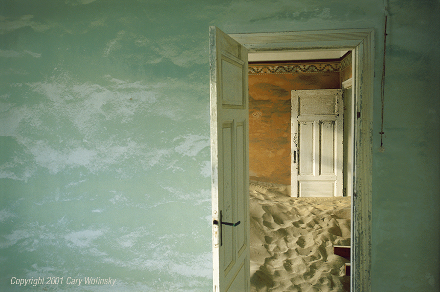 """Sand House Series,  The Green Room. Kolmanskop, near Luderitz, Namibia, 2001:  I stumbled upon Kolmanskop, an abandoned mining town near Luderitz while working on a story about diamonds for the National Geographic Magazine. In 1908, Namibia was still part of German West Africa. A railroad worker was sweeping sand off a stretch of the rail that hugs the coast and where the Namib Desert meets the sea. He picked up a stone that turned out to be a diamond. This single event transformed a country and triggered a rush of prospectors. Workers literally crawled across the desert, shoulder-to -shoulder harvesting stones in concentrations so rich that, in six years, they found more than 4.6 million carats of diamonds. The German government declared a 290 mille long strip of coastal of land, the """"Sperrgebiet,"""" (the Forbidden Zone) where prospecting was forbidden.  Lively mining towns sprung up overnight, littering the desert with housing, casinos and theaters. By the 1930s, new technology had begun to eliminate jobs: machines were being used to mine coastal sands. Workers returned to Germany and wind-driven sands of the Namib swept into the abandoned towns, filling the tidy workers' rooms, and scouring brightly painted walls into dreamscapes.(Photo by Cary Wolinsky, Aurora Photos)"""