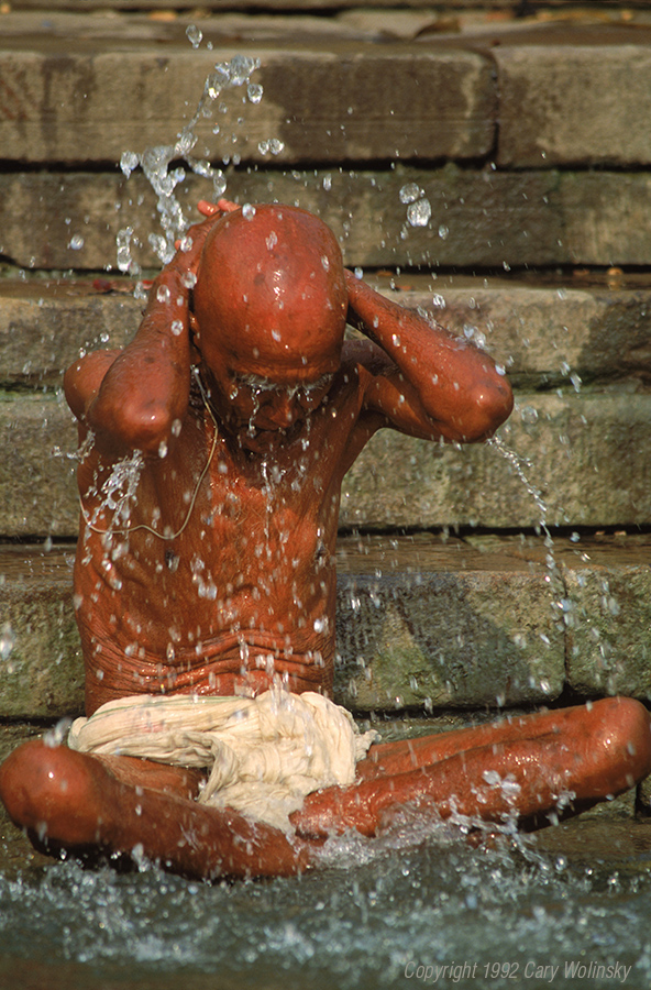 A Indian Hindu holy man performing a customary act of bathing in the Ganges river to cleanse his soul. Varanasi (Benares), India. He is wearing a sutra or sacred thread.
