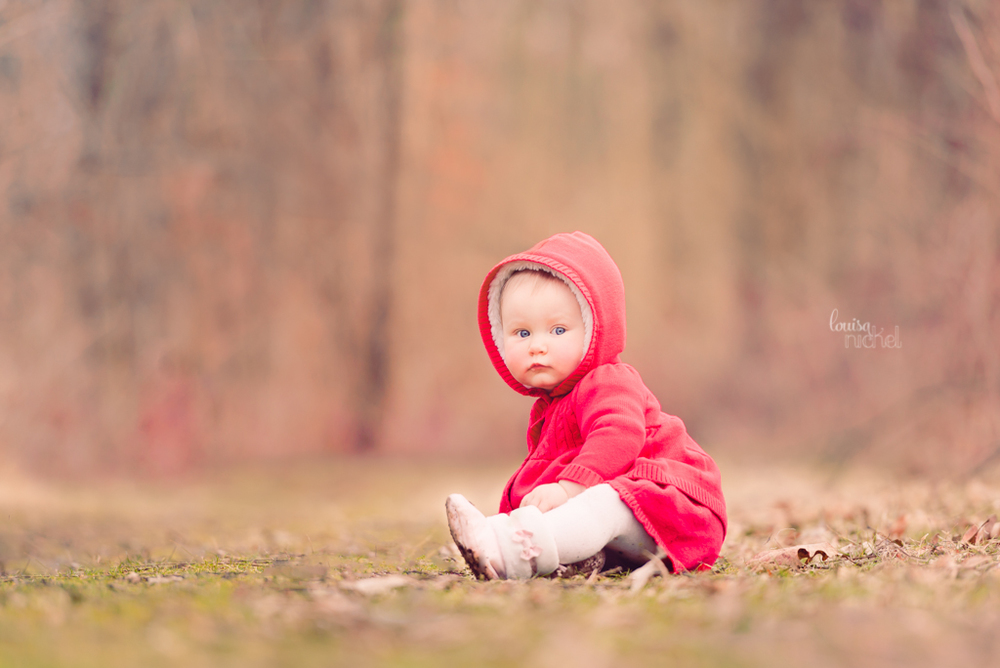 sitting baby girl - outdoors  - red winter coat - Louisa Nickel Photography
