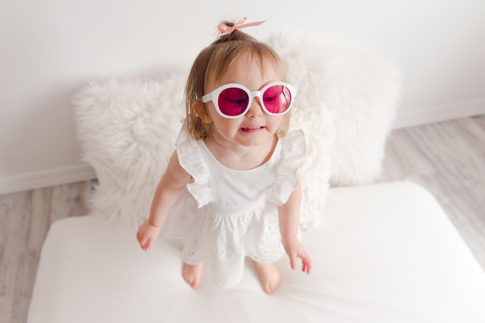 natural light, indoor, 2 year old, girl, white backdrop, white dress, simple, Target, apple, sunglasses, bow, natural poses, ideas, Louisa Nickel Photography, Rockford, Illinois, photographer