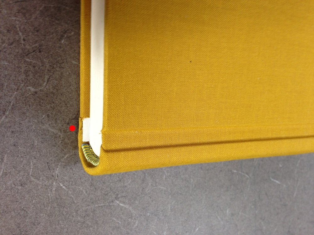 This cut allows the cloth to wrap over the thick board and behind the thin board and spine. Note: because I did not extend my endband along the thin board, I was left with this unsightly exposed board.