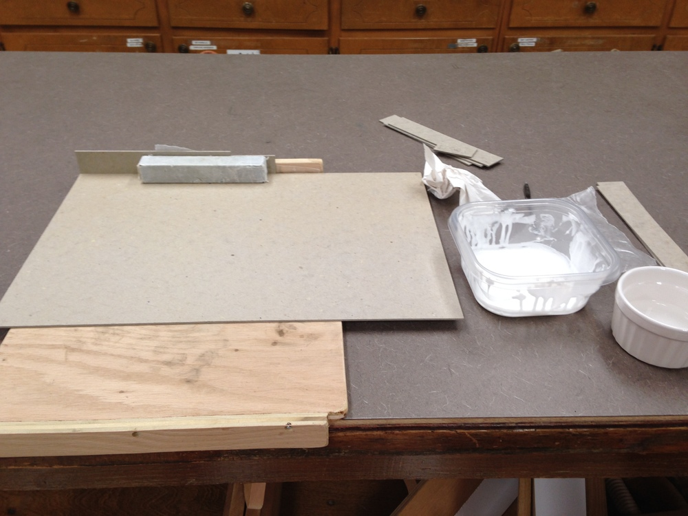 Attaching the walls to the inner tray base using a bench hook and weights for stability.