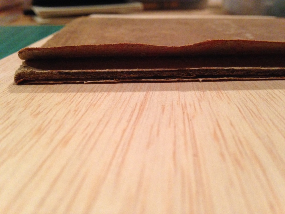 During the rebacking process, I will need to insert new cloth spine material between the cloth and board of the original book covers. The first step is to carefully lift the old cloth from the board.