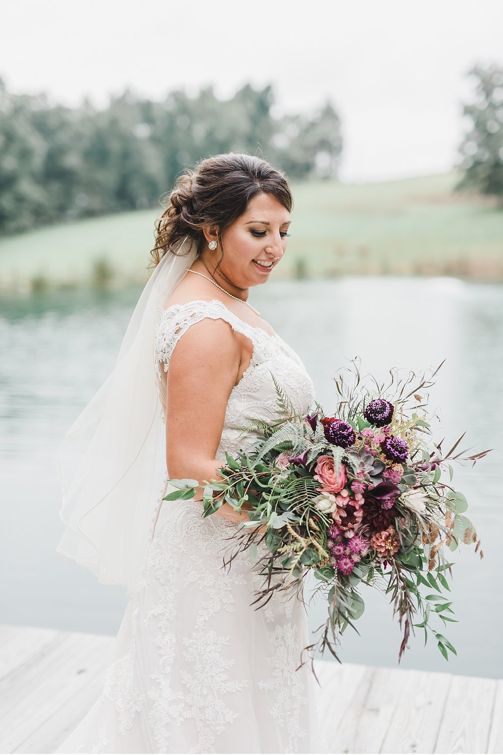 Bride at ponds edge with her bouqet Lancaster Wedding Photographer