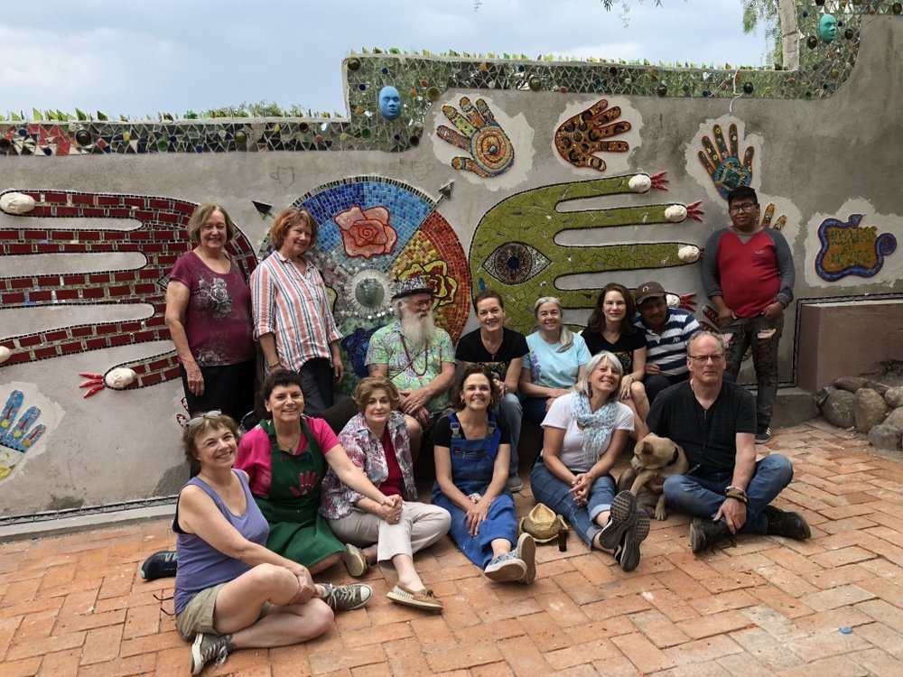 "2018 Crew of Mosaics in Mexico, a hands-on workshop and tour. The ""Big Hands"" wall features designs by each of our artists, complementing the larger hand design."