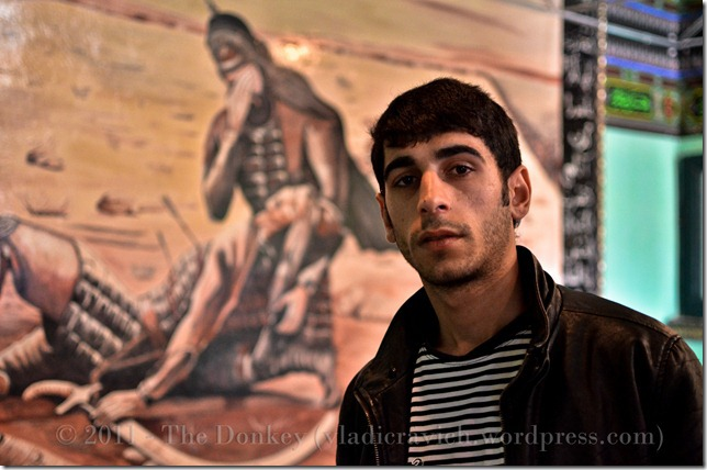 Suleman Kindir in his family's pir, in front of a mural added in the last few years depicting the death of Imam Hussein, a pivotal moment in Shii Islam.