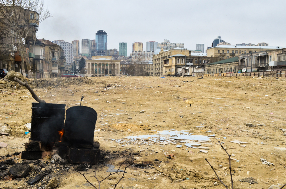 A bucket of tar warming over a flame in a recently demolished block near downtown Baku. Entire sections of the city are being cleared to feed the real estate demands of the recent oil and gas boom.