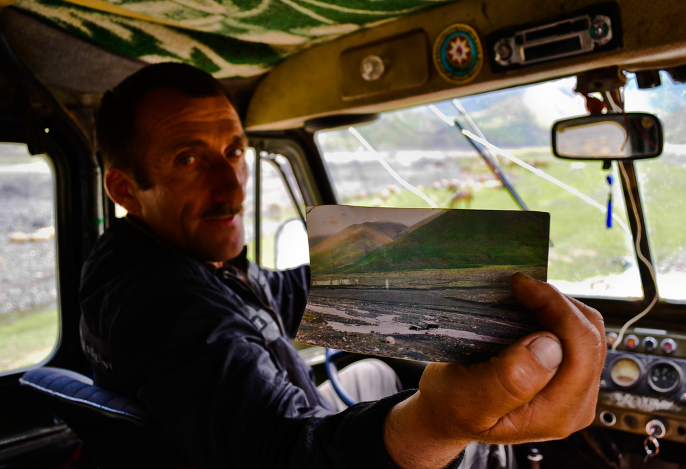 "A tour operator, shows a photo of the same ""soviet jeep"" he currently drives cause in the river before the new 2006 road was opened. He said he took his first foreigner on an adventure tour a decade ago. ""I was so happy I asked for his autograph,"" he said, ""Since then I've taken tourists from 60 countries throughout the mountains."""