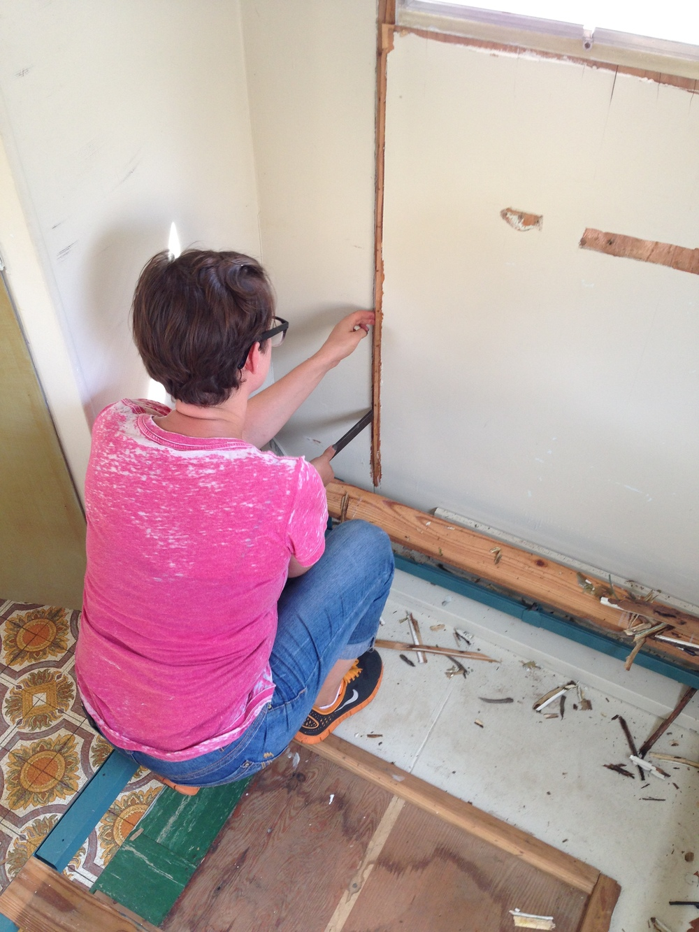 Sarah removing a wall panel with water damage.