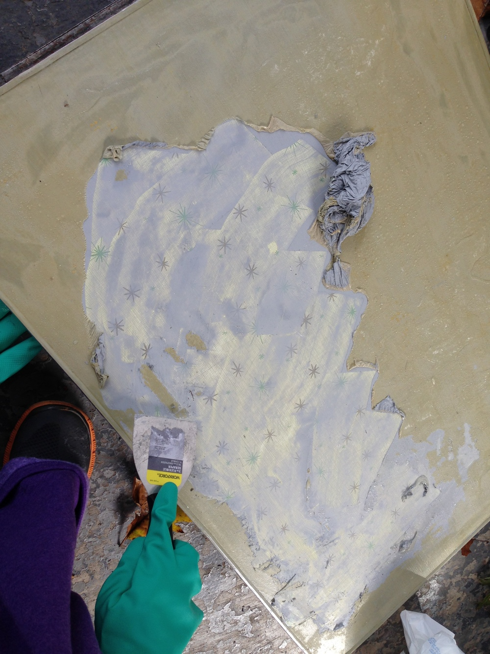 Once the fabric was removed from the table, Sarah stripped old paint off.