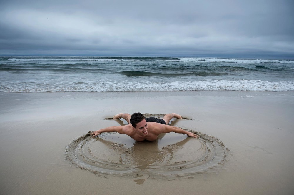 Richard Hardley, of New Zealand, makes a sand angel as his brother John Hardley takes a photo at Huntington State Beach on Wednesday. The two brothers are on vacation. They said we arrived the day it started to rain, we may have brought the rain from New Zealand jokingly. Richard Hardley is all smiles as he says the rain is not going to stop me from swimming in Huntington Beach.