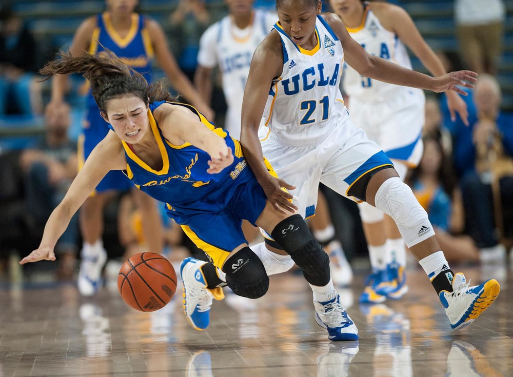 UCR's Annelise Ito dives for the ball against UCLA's Nirra Fields during the second half at UCLA Pauley Pavilion in Los Angeles on Wednesday. UCLA wins with the score of 57 to 43.