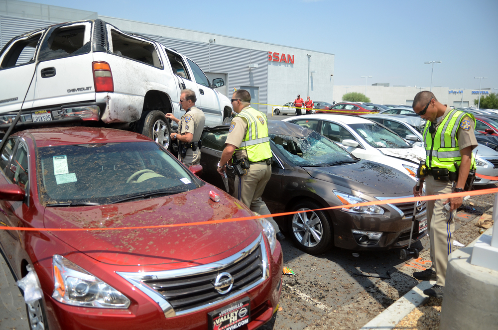 A Chevrolet Suburban had a right rear tire blowout when the driver lost control, hitting the center divider and veering across Interstate 15 and rolling onto vehicles at the Nissan Dealership in Victorville, Calif, on Sunday, July 19, 2015. A child was ejected in the crash, sustaining major injuries and was transported by Mercy Air. 