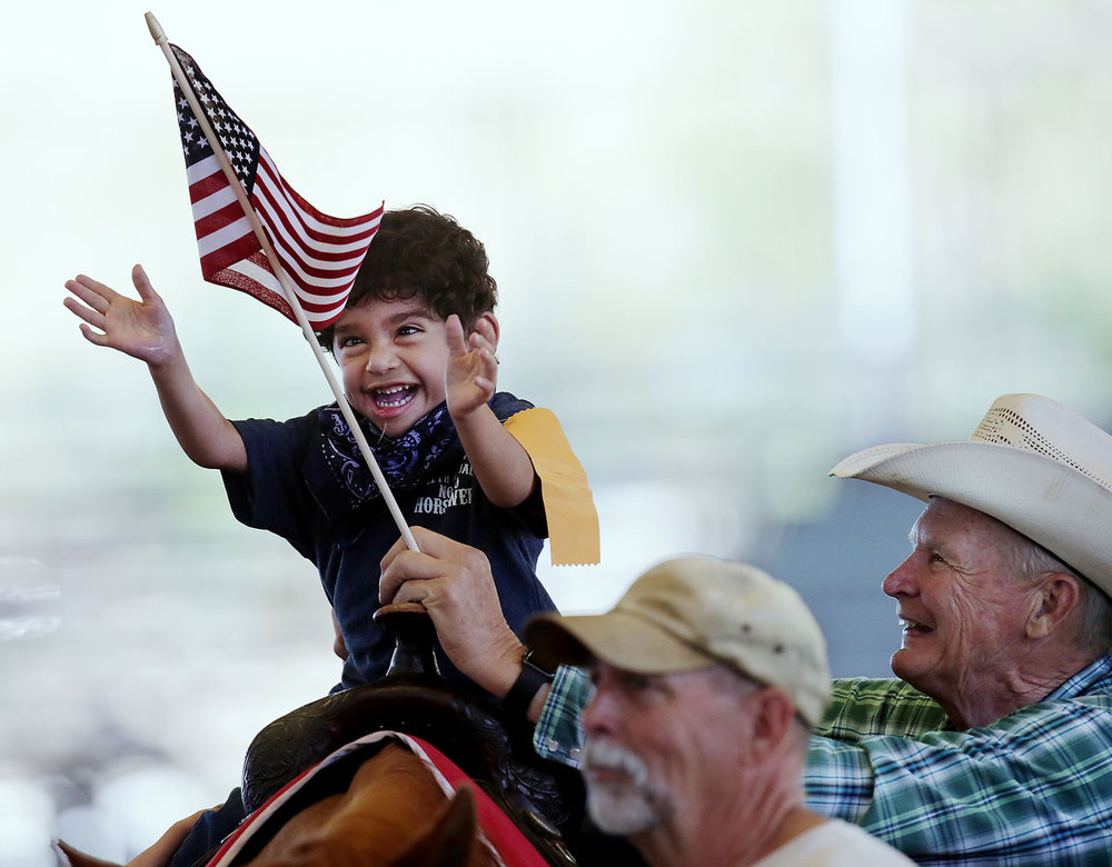 Giovanny Lizardi, 5, of San Bernardino enjoys a ride on a real horse as he reaches for a flag as he enjoys Challenged Children's Rodeo for special needs kids at Ingalls Park in Norco, CA. Sunday, Apr. 23, 2017.