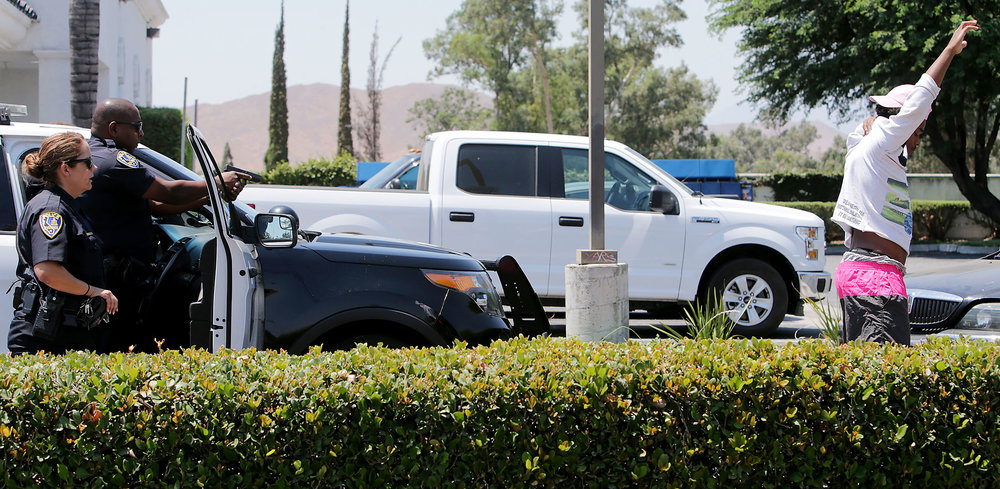 Riverside police officers with guns drawn have a suspect walk backwards to them after he and three others were ordered to leave a black sedan at gun point in the parking lot of Bakers restaurant on Main Street south of the east bound 60fwy off ramp around 1:40p.m. Tuesday in Riverside, CA. July 11, 2017. 