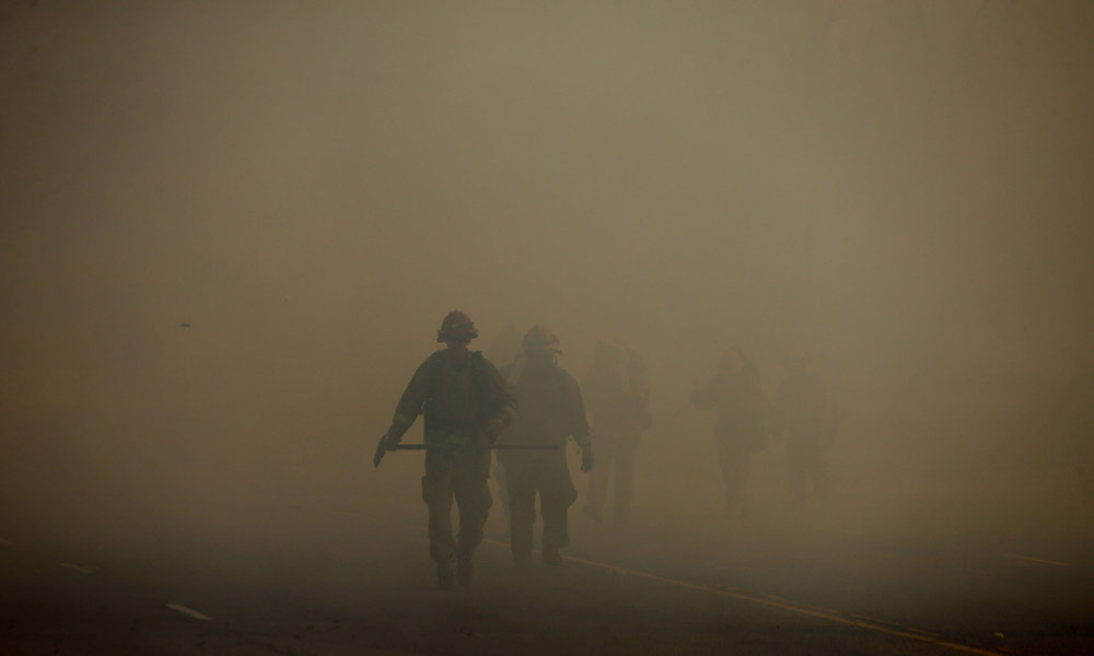 A inmate brush crew makes their way through the heavy smoke as they head to fight the Riverbottom fire Thursday in Riverside, CA. December 21, 2017.