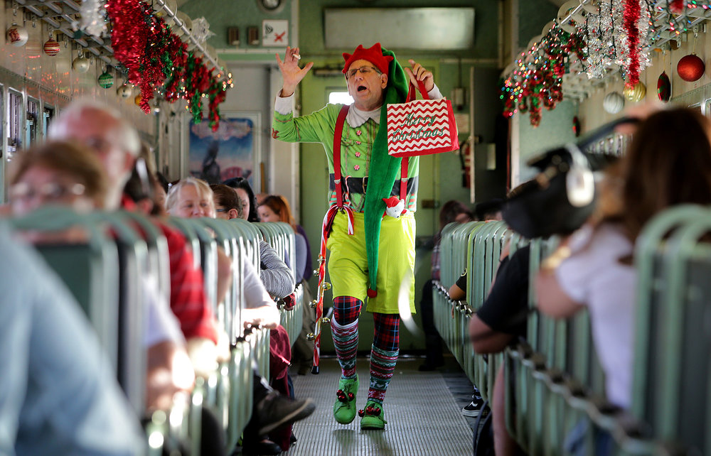 """Ken Schwartz plays Jingles the elf as he sings and dances for guests on the train during """"Take a Train to Santa's Workshop"""" at Orange Empire Railway Museum Sunday in Perris, CA. December 3, 2017."""