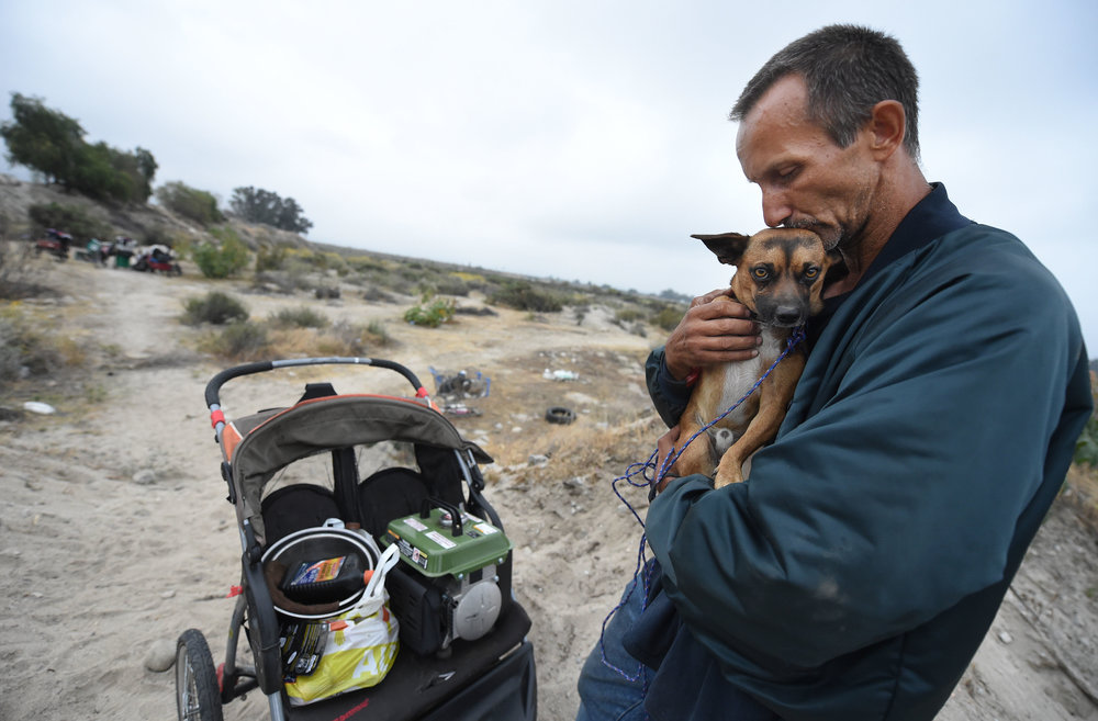 Robert Cervantes, 47, kisses his dog Threefur, after removing his belongs from a homeless camp in the Santa Ana River bed Thursday morning. The Redlands police department along with assistance from San Bernardino County Flood Control and the Redlands Quality of Life department, began the removal of homeless structures and camps in the Santa Ana River area of Redlands Thursday May 31, 2018. Homeless residents were told last Thursday they had 72 hours to pack up their belongs. The approximately 14 homeless residents were given the opportunity to accept hotel vouchers and other assistance.