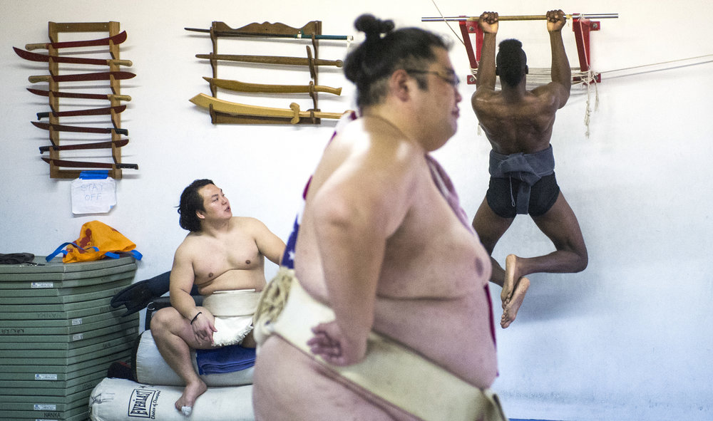 "Two-time World Sumo Champion Yamamotoyama or Yama, center, watches the sumo ring as Compton native Phillip ""Monster"" Barnes, of Compton, do pull-ups and  Takeshi Amitani, of Japan, looks on during a sumo wrestling practice in Carson Sunday, April 8, 2018. Amitani coaches and trains with Monster as the two will enter the same weight class this year for the US Sumo Open. Amitani is a 5-time Japanese National University Champion, he also was the undefeated Openweight champion in the  US Sumo Open last year. This will be Monster's second sumo competition."