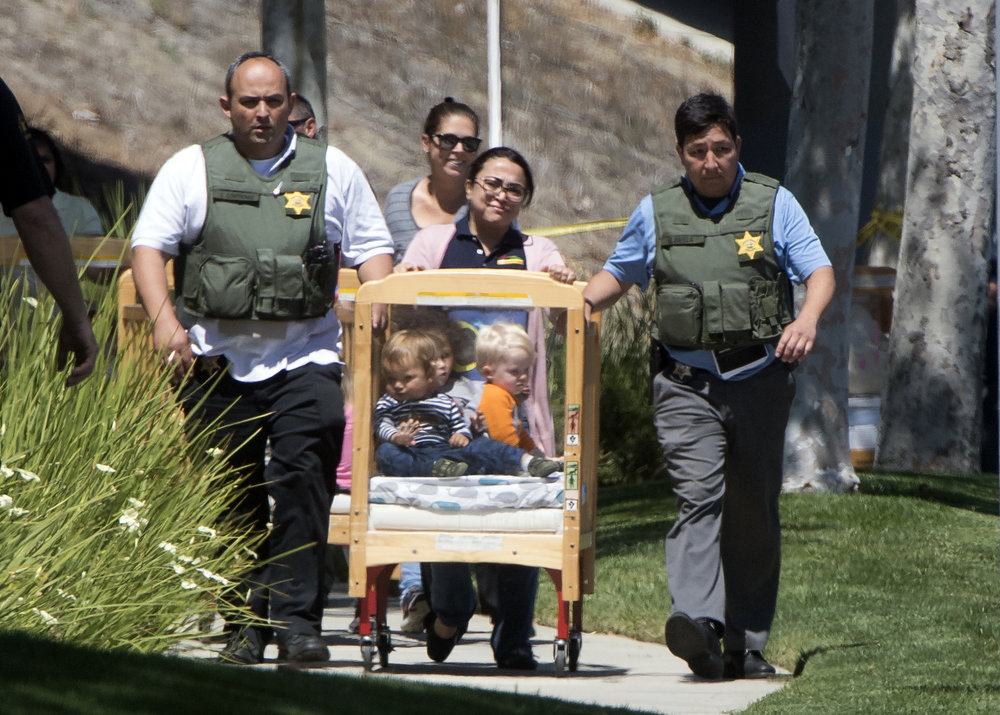 Sheriff deputies escort children from a preschool to a nearby Target where their parents picked them up after an explosion in Aliso Viejo on Tuesday, May 15, 2018.