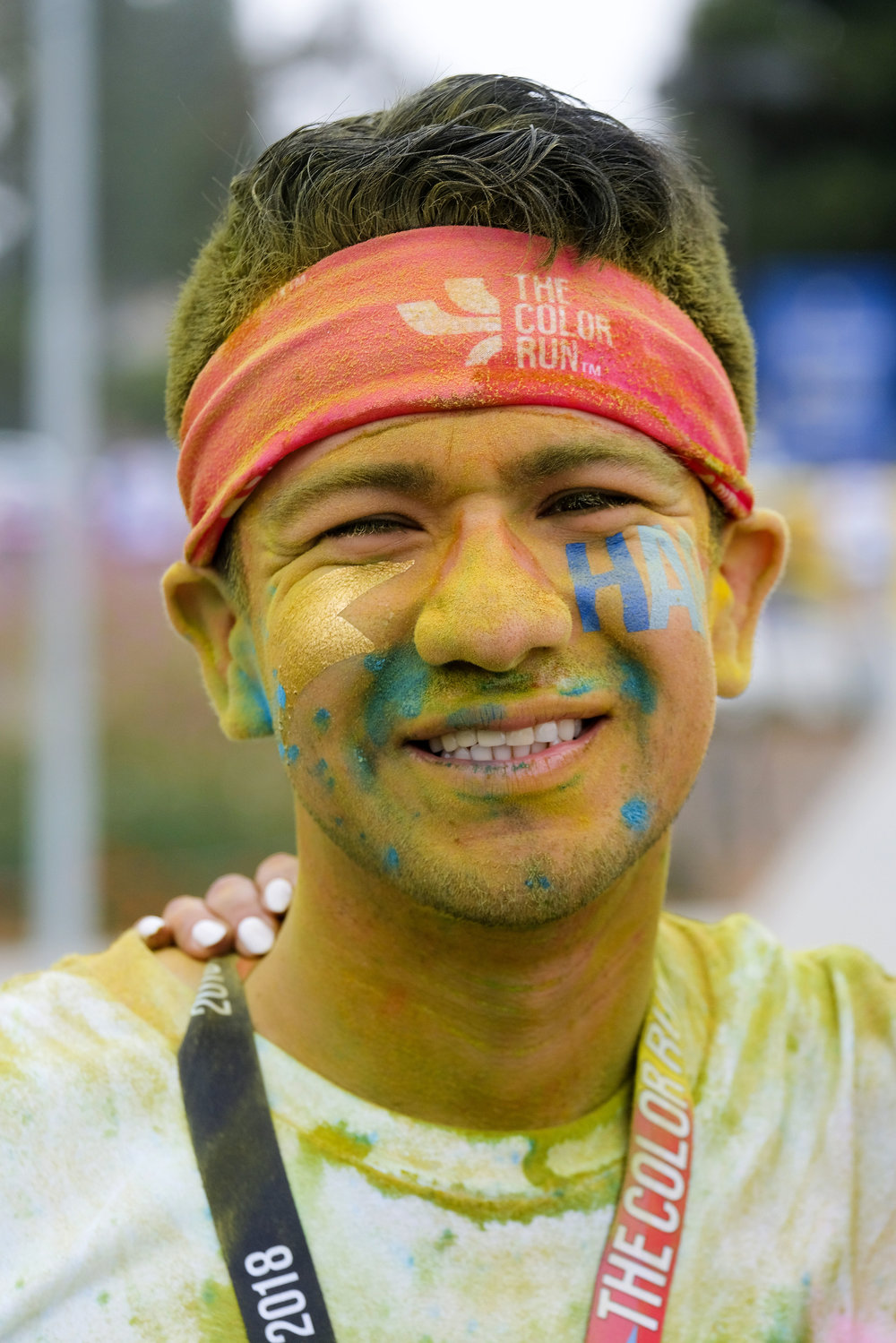 A runner covering with color powder on her face in the Color Run at the StubHub Center in Los Angeles, United States, June 23, 2018.