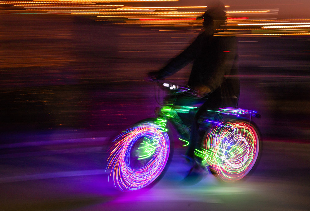 A bicyclist with lights rides past while righting through Shoreline Village in Long Beach Wednesday night July 4, 2018.