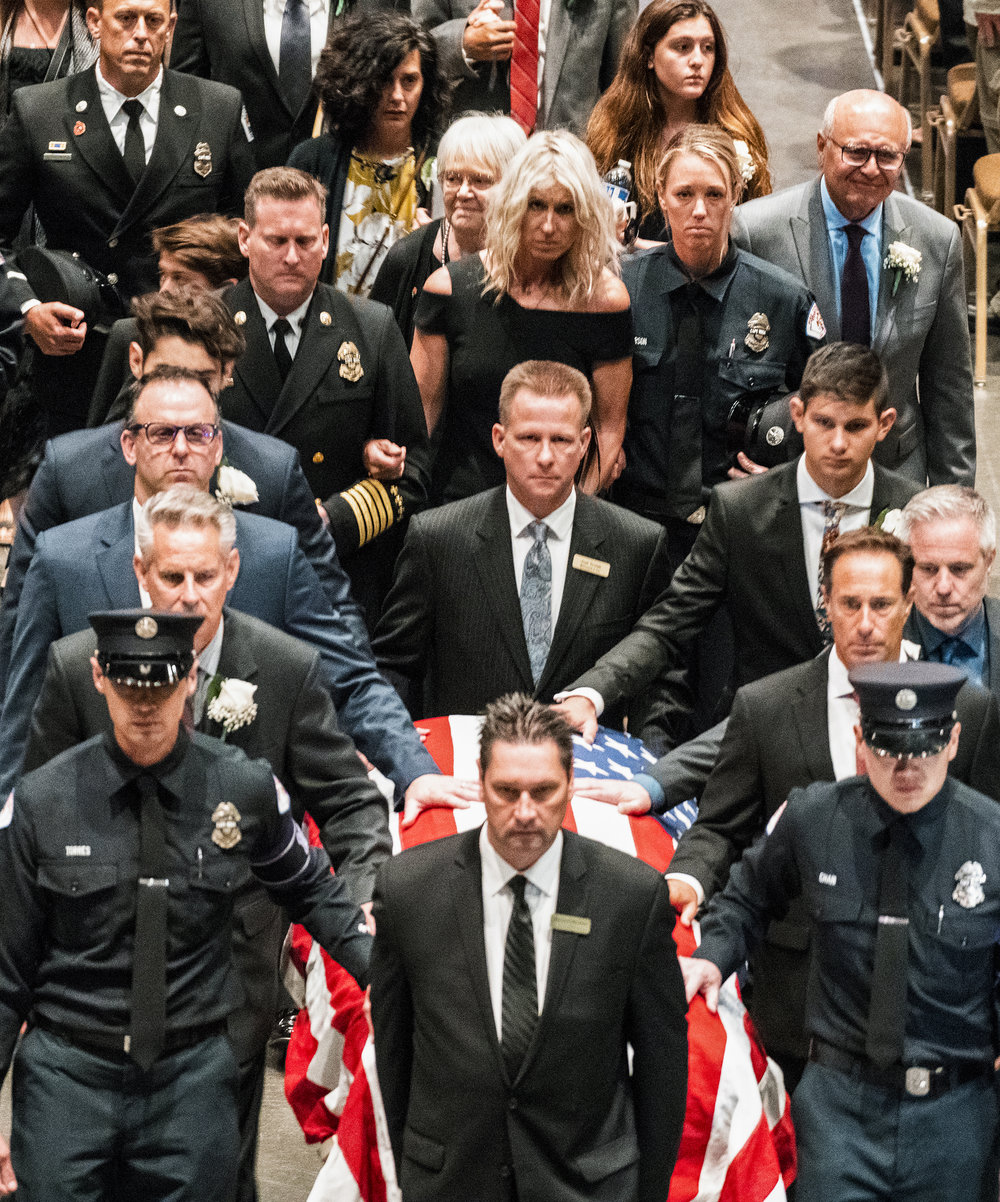 The Rosa family walks behind the casket of Long Beach Fire Captain David Rosa as thousands attend the memorial service in Long Beach July 3, 2018. Rosa was shot around 4 a.m. on June 25, while responding to a fire at a senior-living home in Downtown Long Beach. Authorities have charged a 77-year-old man, Thomas Kim, with murder and arson for allegedly setting off a bomb in his apartment before opening fire.