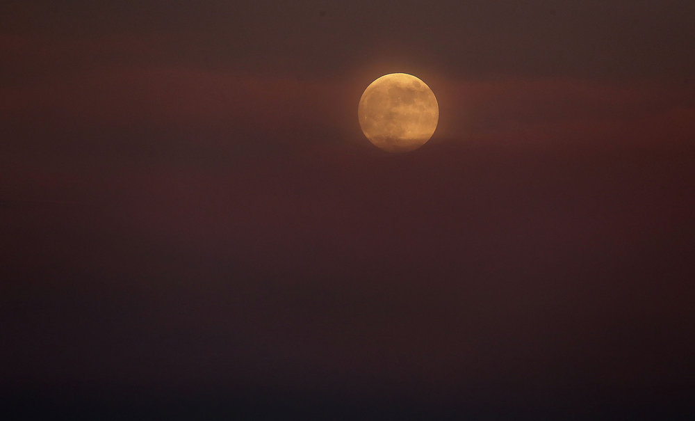 The full moon rises in the colorful smoke from the Cranston fire in the San Bernardino National Forest above Lake Hemet on Thursday, July 26, 2018.