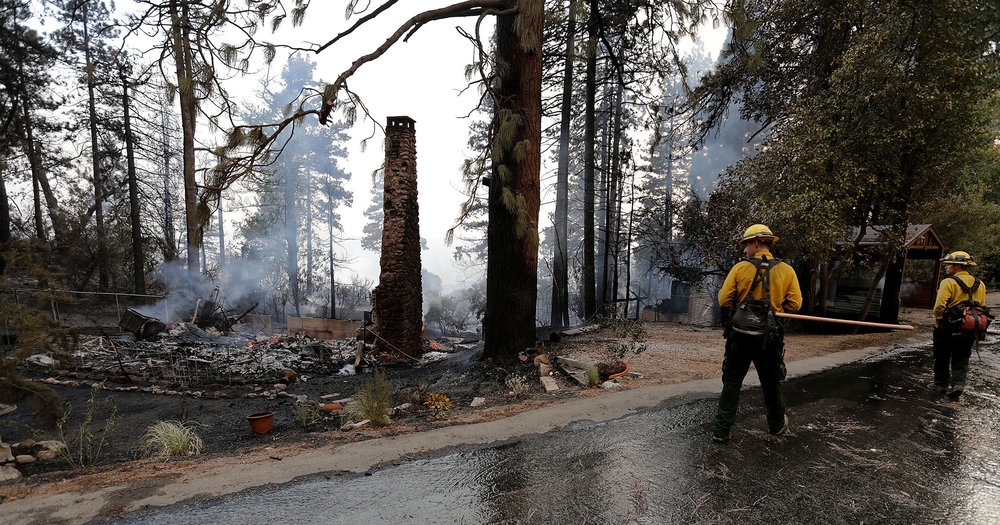 CalFire fighters walk past and look at one of the homes that was unable to be saved on Deer Foot Lane during the fast moving Cranston fire as it grows to more than over 3,500 acres in the San Bernardino National Forest in Idyllwild on Wednesday, July 25, 2018.